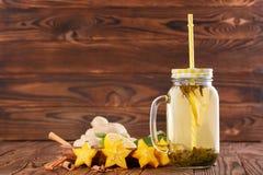 Té verde del limón en un tarro de cristal grande con la paja al lado del limón, del canela, del jengibre, y del carambola cortado Imagen de archivo libre de regalías