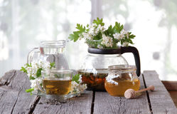 Té verde en una taza de cristal, miel y una rama de un espino floreciente Foto de archivo libre de regalías