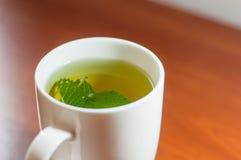 Té verde en una taza en una tabla de madera fotografía de archivo libre de regalías