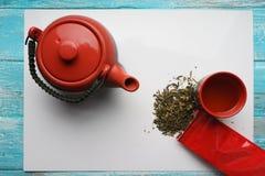 Té verde, primer, hojas secas de la visión superior, tetera, una taza de té, y bolso rojo del embalaje en el fondo blanco Fotografía de archivo libre de regalías