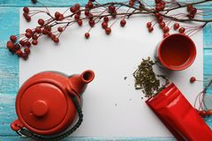 Té verde, primer, hojas secas de la visión superior, tetera, una taza de té, y bolso rojo del embalaje en el fondo blanco Imagenes de archivo