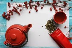 Té verde, primer, hojas secas de la visión superior, tetera, una taza de té, y bolso rojo del embalaje en el fondo blanco Imágenes de archivo libres de regalías