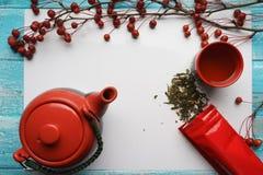 Té verde, primer, hojas secas de la visión superior, tetera, una taza de té, y bolso rojo del embalaje en el fondo blanco Fotos de archivo libres de regalías