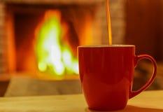 Té, vertiendo a la taza roja, bajo fondo acogedor de la chimenea Foto de archivo libre de regalías