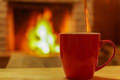 Té, vertiendo a la taza roja, bajo fondo de la chimenea Imágenes de archivo libres de regalías