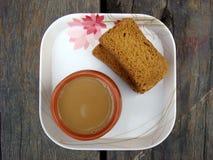 Té y bizcocho tostado en la placa blanca Imagen de archivo