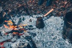 Té y café en el fuego Un pote y un turco en un fuego al aire libre Fotos de archivo