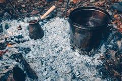 Té y café en el fuego Un pote y un turco en un fuego al aire libre Imagenes de archivo