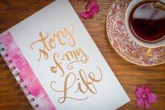 Té y diario calientes de arriba con las flores rosadas imagenes de archivo