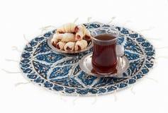 Té y galletas, servidos en el platemat qalamkar. imagen de archivo
