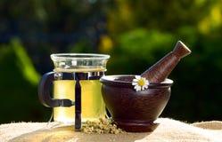 Té y maja de madera con las manzanillas fotografía de archivo