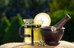 Té y maja de madera con las manzanillas foto de archivo