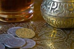 Té y monedas sobre una bandeja Imágenes de archivo libres de regalías