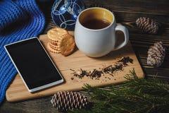 Té y smartphone en el centro de la decoración linda de la Navidad Imagen de archivo