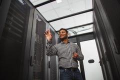 Técnico alegre de las TIC que estima el armario del servidor fotografía de archivo libre de regalías