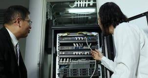 Técnico asiático de Internet que usa el cuaderno y comprobando el gabinete de módem y explicar cómo trabaja a su jefe almacen de metraje de vídeo