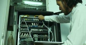 Técnico asiático do Internet que verifica o armário de modem video estoque