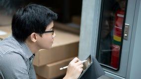 Técnico asiático que verifica o armário da mangueira de fogo fotografia de stock