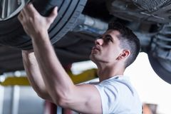 Técnico automotriz que cambia una rueda Foto de archivo libre de regalías