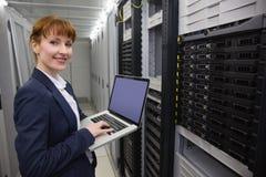 Técnico bonito que usa o portátil ao trabalhar em servidores Fotos de Stock Royalty Free