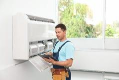 Técnico con el tablero cerca del acondicionador de aire foto de archivo libre de regalías