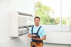 Técnico con el tablero cerca del acondicionador de aire imágenes de archivo libres de regalías