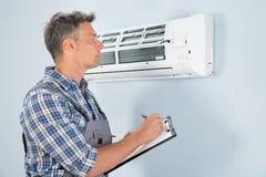Técnico con el tablero que mira el acondicionador de aire Foto de archivo libre de regalías