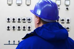 Técnico con los instrumentos de control del casco azul en central eléctrica Fotos de archivo libres de regalías