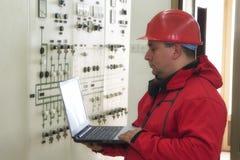 Técnico con los instrumentos de la lectura del ordenador portátil en contro de la central eléctrica Imágenes de archivo libres de regalías