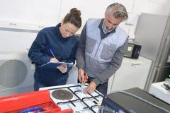Técnico da mulher e do homem que verifica dispositivos na cozinha imagens de stock