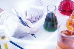 Técnico de laboratório fêmea Dealing With Flasks que contém produtos químicos líquidos foto de stock