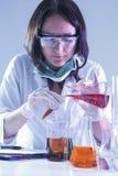 Técnico de laboratório fêmea With Flasks Filled com os produtos químicos líquidos que conduzem a experiência imagem de stock