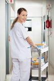 Técnico de laboratório Pushing Medical Cart no corredor Fotos de Stock
