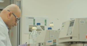 Técnico de laboratório que trabalha com espectrómetros maciços em um laboratório da companhia farmacéutica vídeos de arquivo