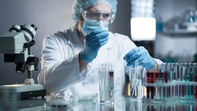 Técnico de laboratorio que mide la fórmula exacta para los productos cosméticos hipoalérgicos imagenes de archivo