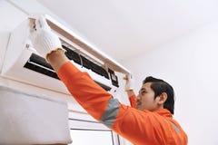 Técnico de sexo masculino asiático joven que repara el acondicionador de aire imagenes de archivo