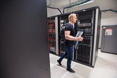 Técnico de sexo masculino Carrying Blade Server mientras que camina en Datacente Imagen de archivo libre de regalías