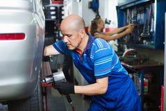 Técnico de sexo masculino maduro que cabe el nuevo neumático del coche imagen de archivo libre de regalías