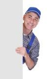 Técnico de sexo masculino maduro que señala en cartel Foto de archivo libre de regalías