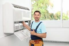 Técnico de sexo masculino que coloca el acondicionador de aire cercano fotografía de archivo