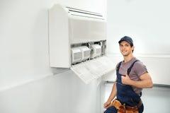 Técnico de sexo masculino que coloca el acondicionador de aire cercano imagen de archivo