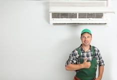 Técnico de sexo masculino que coloca el acondicionador de aire cercano foto de archivo libre de regalías