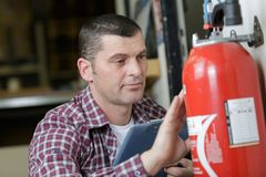 Técnico de sexo masculino que comprueba el extintor que escribe en el documento foto de archivo libre de regalías