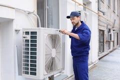 Técnico de sexo masculino que repara el acondicionador de aire foto de archivo