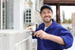 Técnico de sexo masculino que repara el acondicionador de aire imagen de archivo libre de regalías