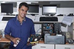 Técnico del ordenador con la placa madre en el taller Fotografía de archivo
