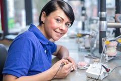 Técnico dental que aplica a cera a um molde para produzir um prothesis Imagens de Stock