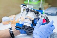 Técnico dental que trabaja con el órgano articulador en laboratorio dental imágenes de archivo libres de regalías