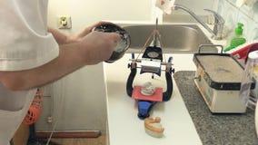 Técnico dental que trabaja con el órgano articulador en laboratorio dental almacen de metraje de vídeo