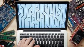 Técnico do computador da vista superior que usam o laptop com esboço da placa de circuito na mesa de madeira com ferramentas e el video estoque